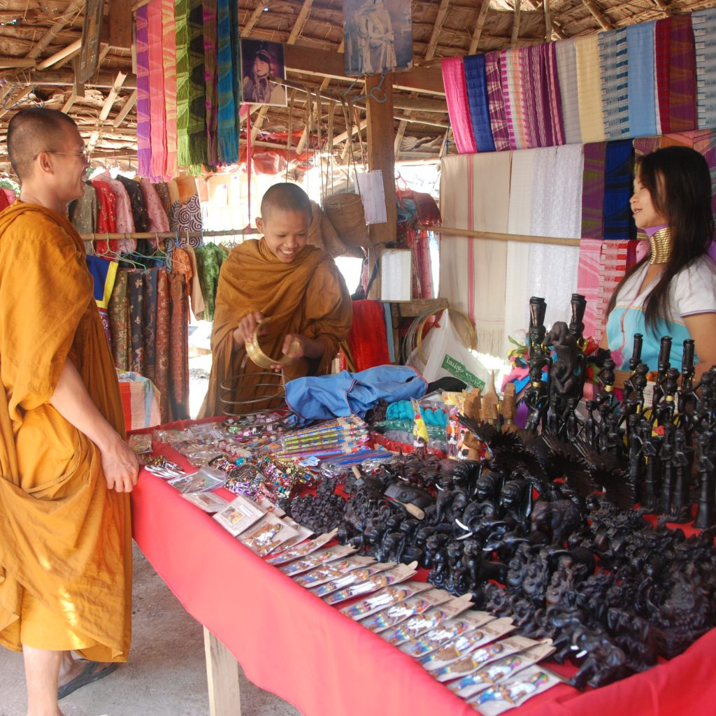 Monks Who Come To Huay Sua Thao As Tourists, That Is A Scene, Which The Average Western Person Might Not Expect. Maya Helps These Monks To Find Something At Her Shop. Maya Made The Scarves In The Background Herself, The Souvenirs On The Table Come From Chiang Mai, The Big City Of The North. The Women Have To Sell These Souvenirs With Profit, Which Is Often Relatively Little. Photo By: Charlotte Louwman-Vogels