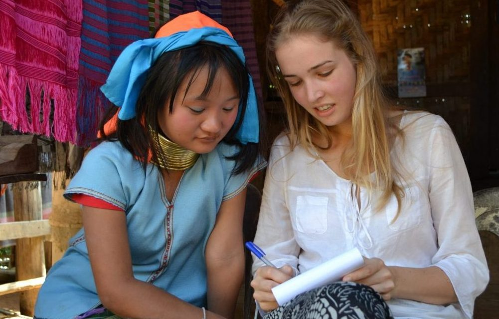 This is Muko, 16 years old and here you can see that  she learns some Dutch words from Renske. Muko says that she does not go to school and that she learned English from tourists. She enjoys communicating with them and to learn some words and small phrases in their language. Even though it is a lot of fun to talk to the Kayan, it might not always be that easy to make that contact as a tourist. You can say at lot though by gesturing and in the end your attempts will always be appreciated! Photo by: Joney Habraken